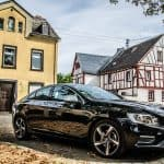 Black 2016 Volvo S60 in front of house